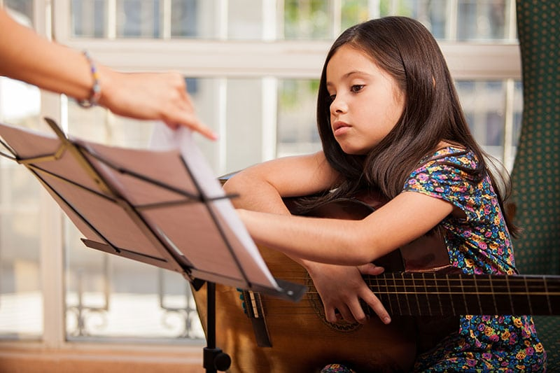 liitle girl learning guitar